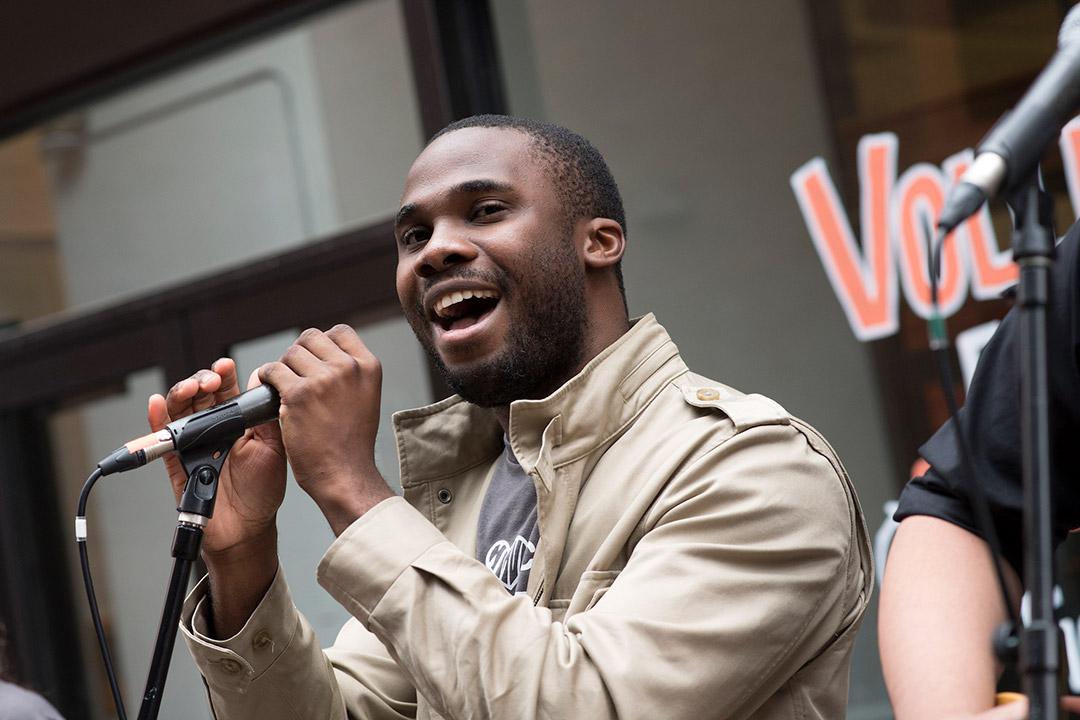 """Adesola """"Dewé"""" Adedewe sings into a microphone."""