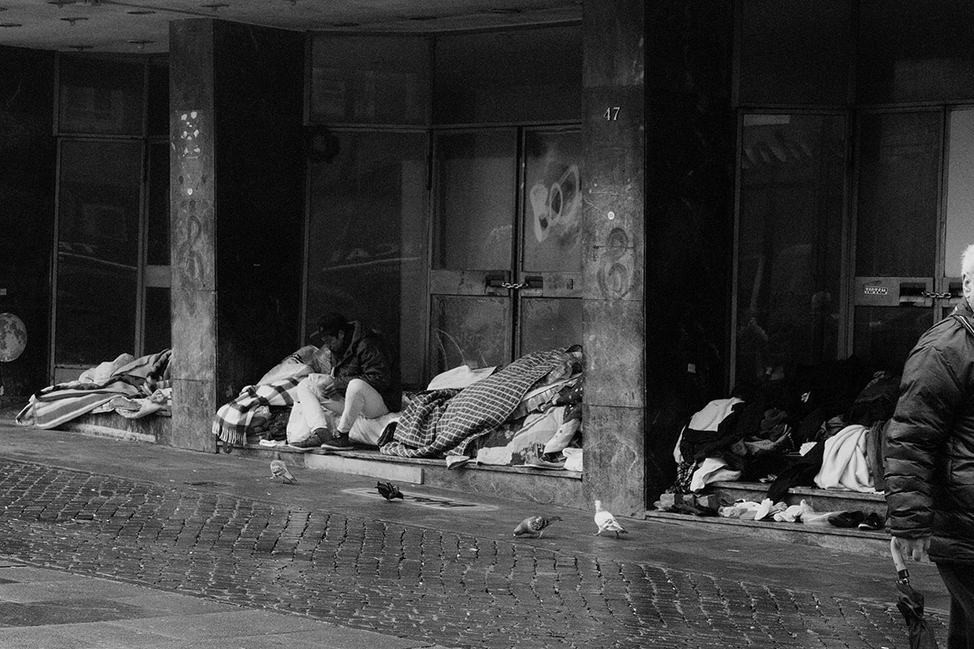 Homeless people with blankets near doors of building.