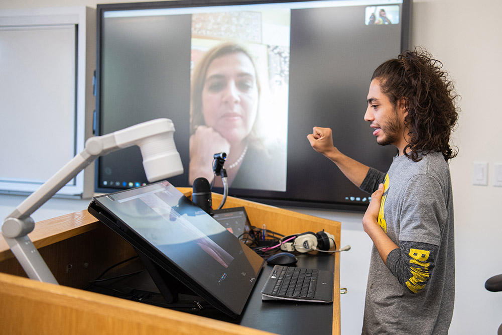 Student speaks with woman in Italy though videoconferencing equipment.
