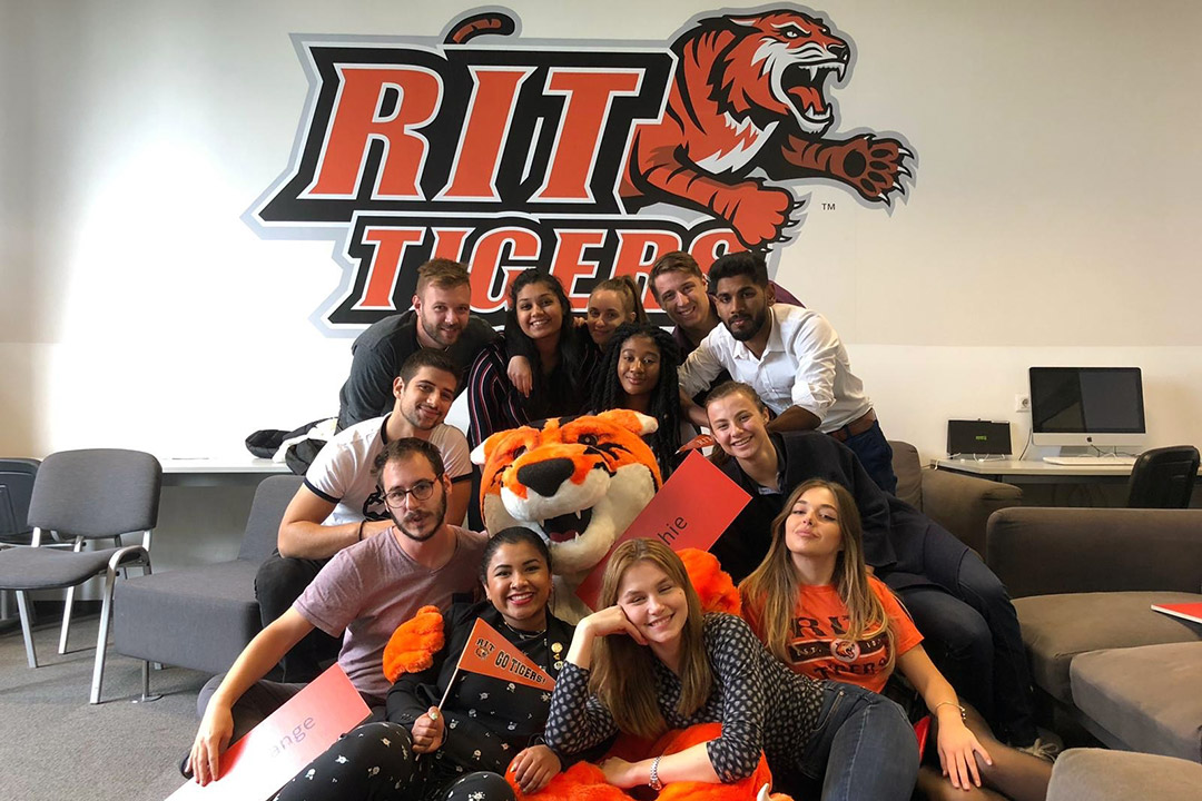 Students pose wth tiger mascot in front of RIT Tigers logo on wall.