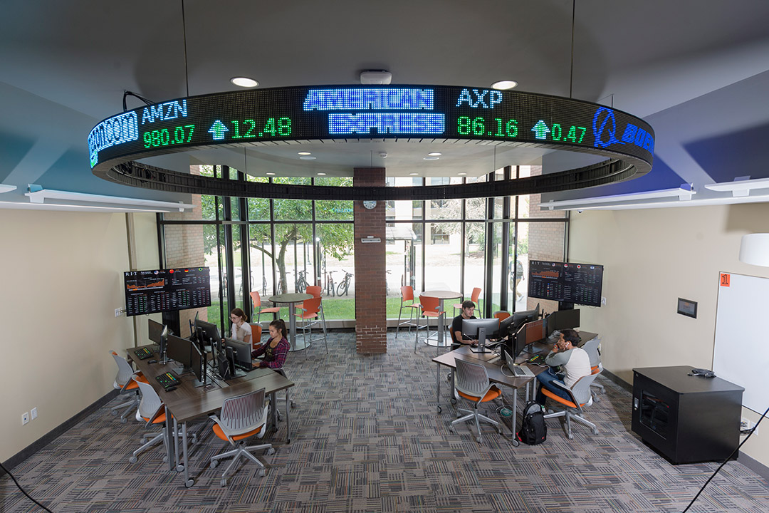 open lab with two computer workstations and digital stock ticker.