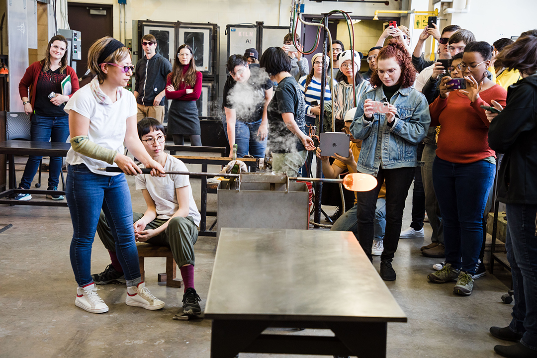 Aya Oki leads a demo for a crowd of people in RIT's hot shop.
