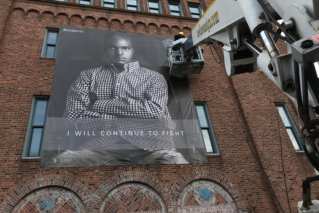 Giant portrait of young man being installed on exterior brick wall.