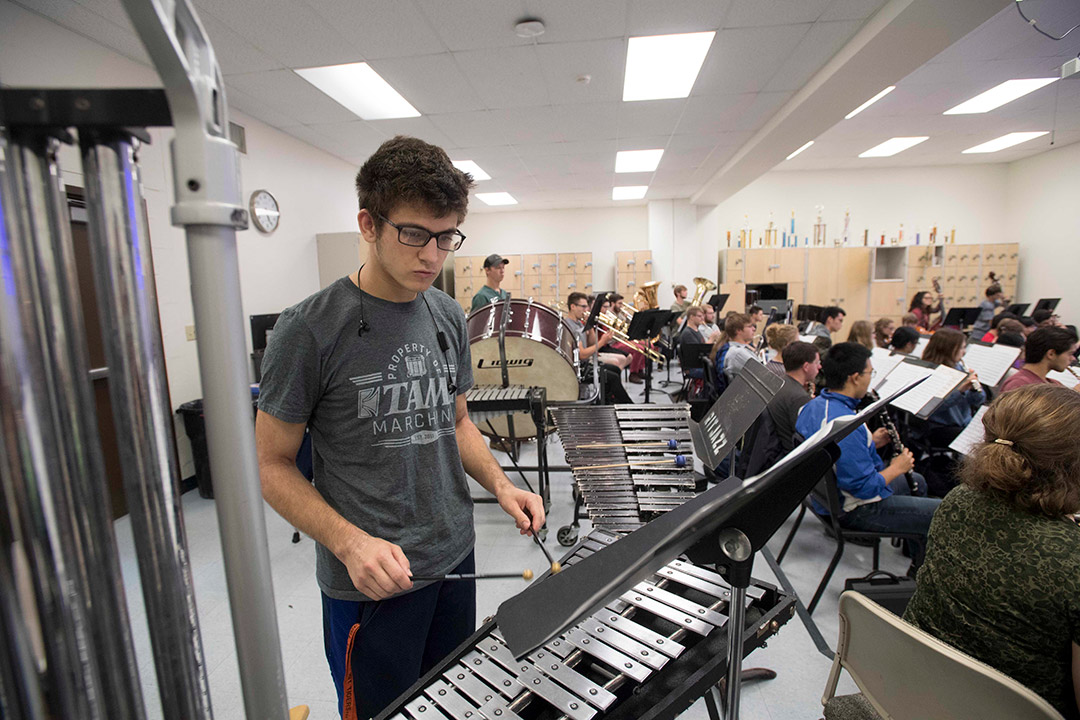 'Student plays xylophone in orchestra.'