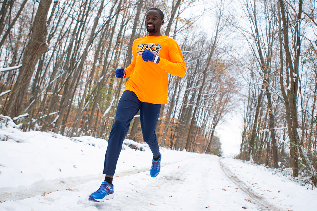 'Student jogging outside on snowy path.'