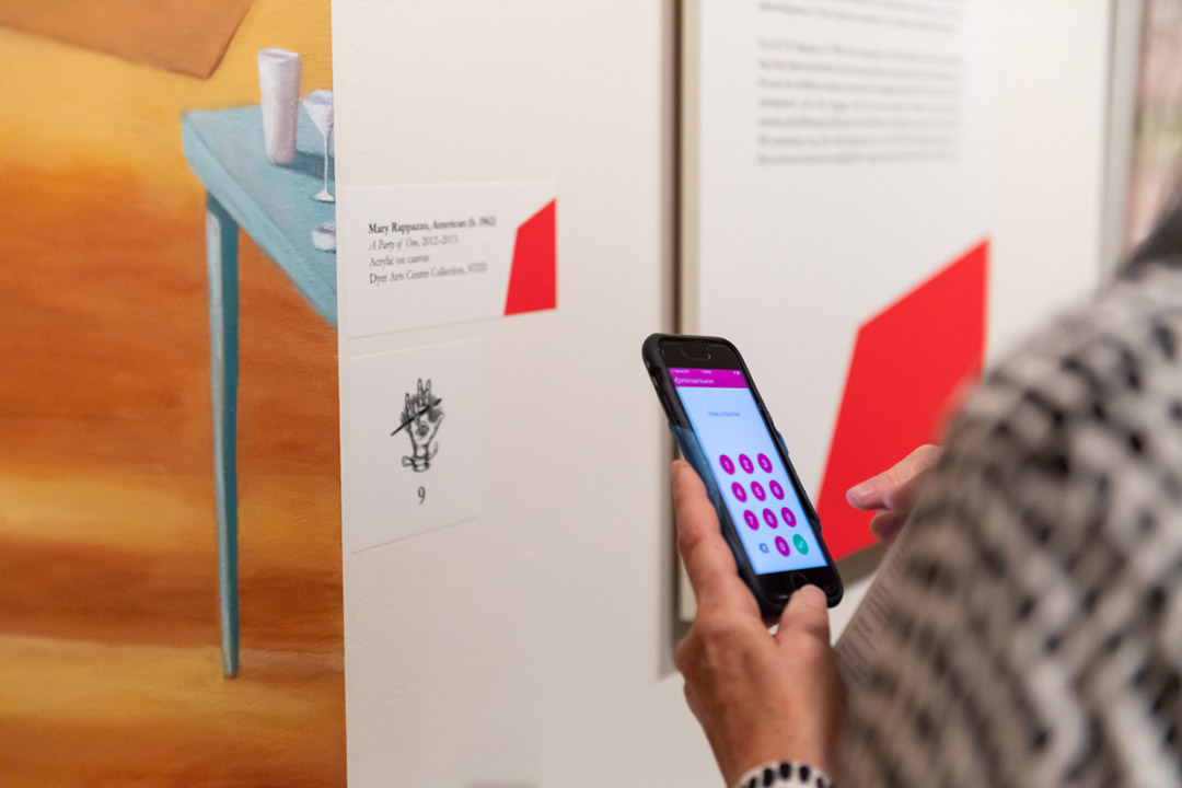 Person using app on smartphone to scan number next to piece of art.