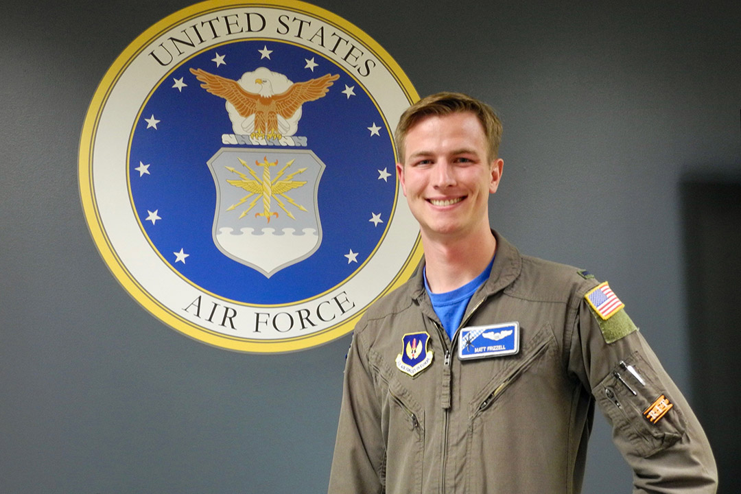 U.S. Air Force member stands in front of Air Force seal.