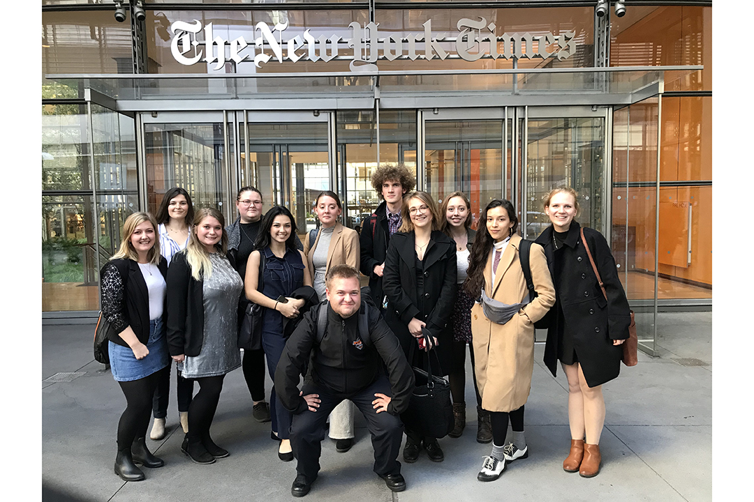 'Students gather for a group photo in front of The New York Times.'