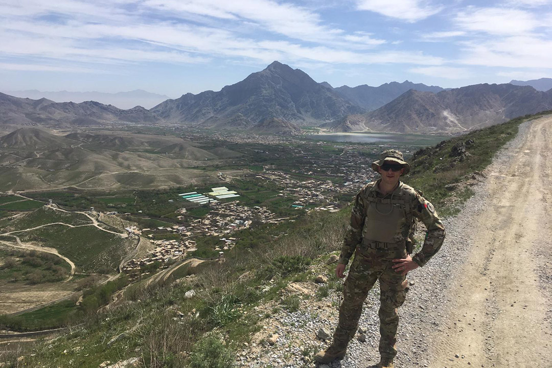 'American soldier stands on roadside with mountains in background.'