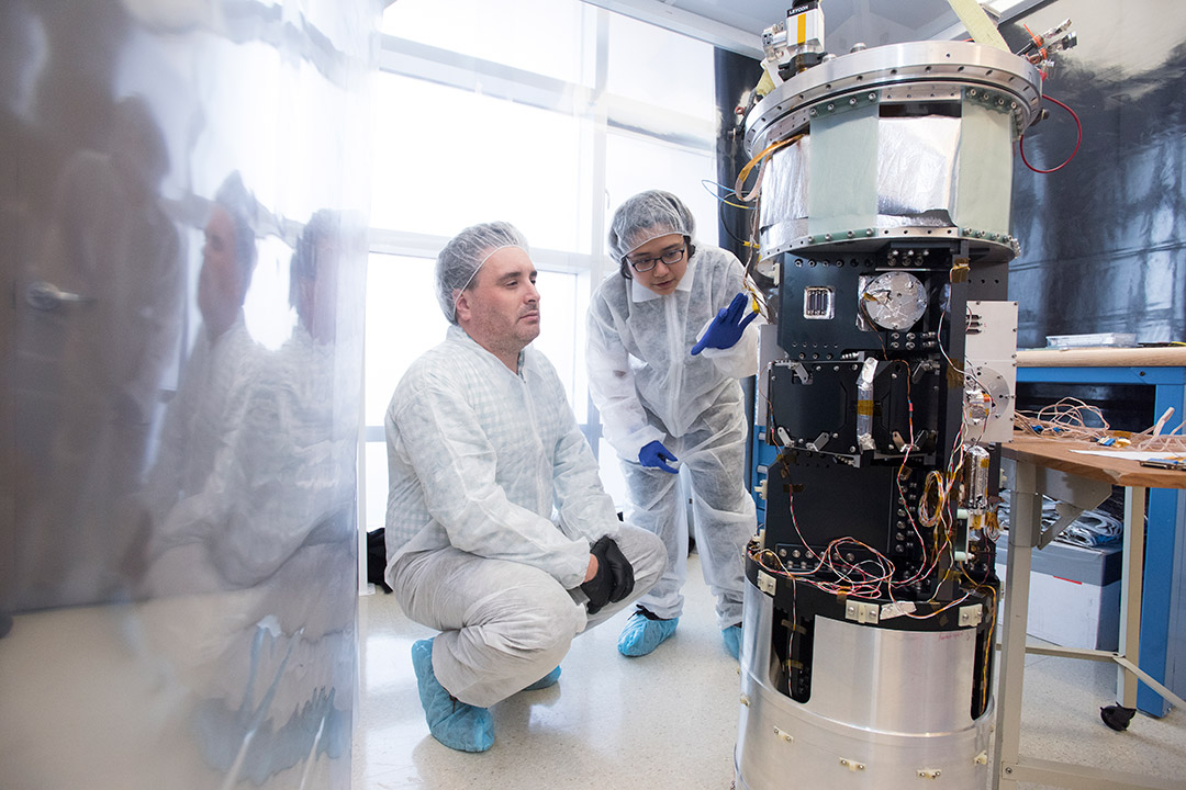 'Two researchers wearing cleansuits work on detector equipment.'