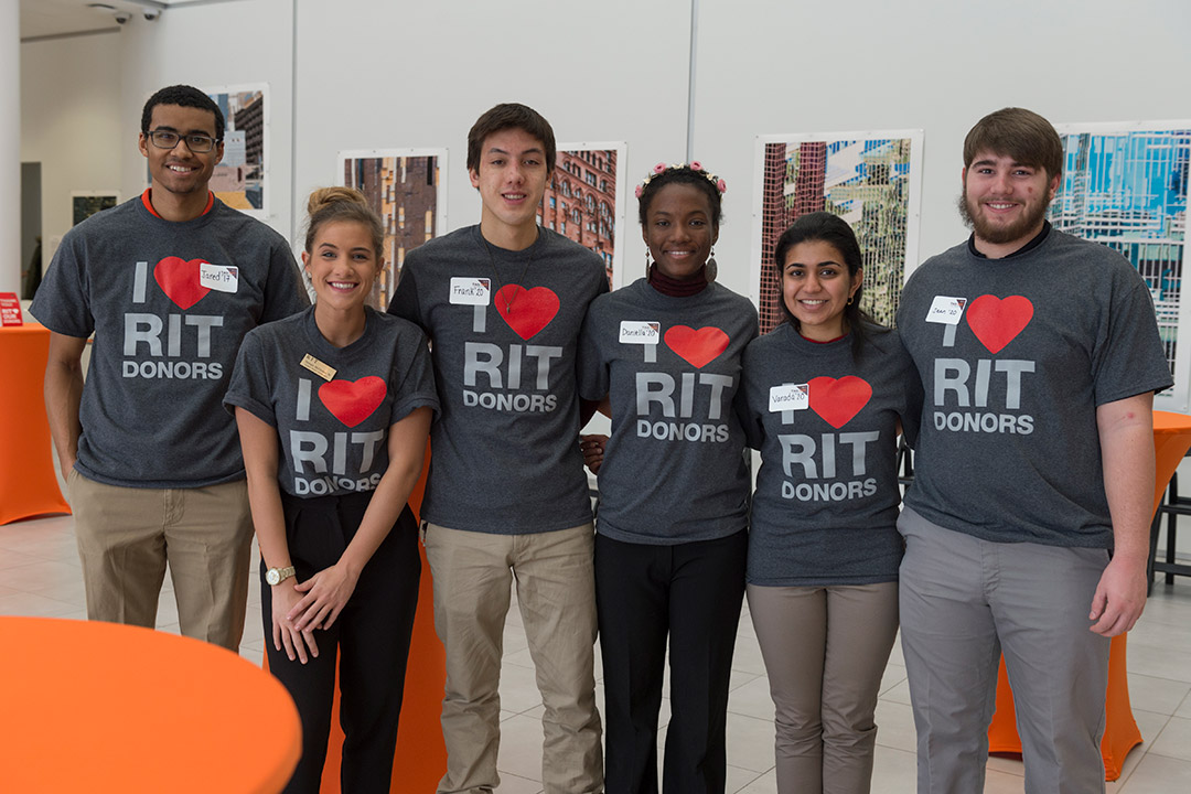 'group of six students standing together wearing gray T-shirts that say I heart RIT donors.'