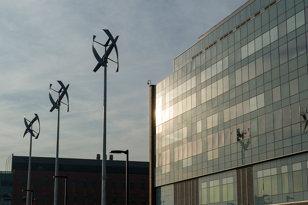 Three wind turbines in front of glass building.