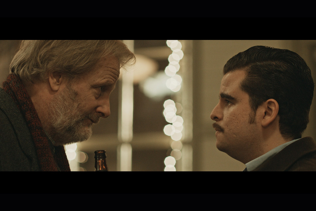 Screenshot from movie in which two actors look face-to-face.