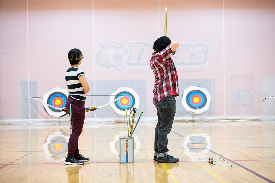 'two students in archery class aim arrows at targets.'
