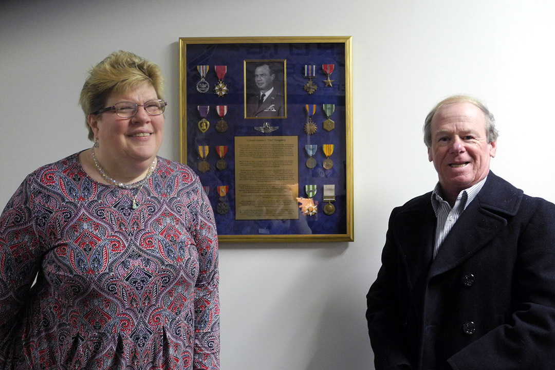 man and woman standing next to display of military medals.