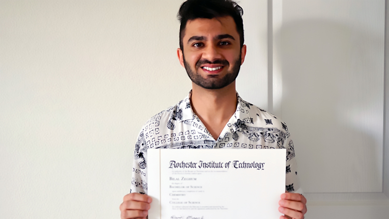 student holding a degree