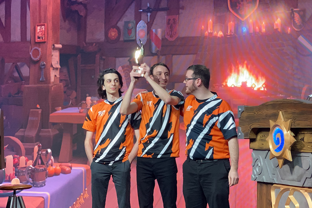 three e-sports players holding up trophy on stage.