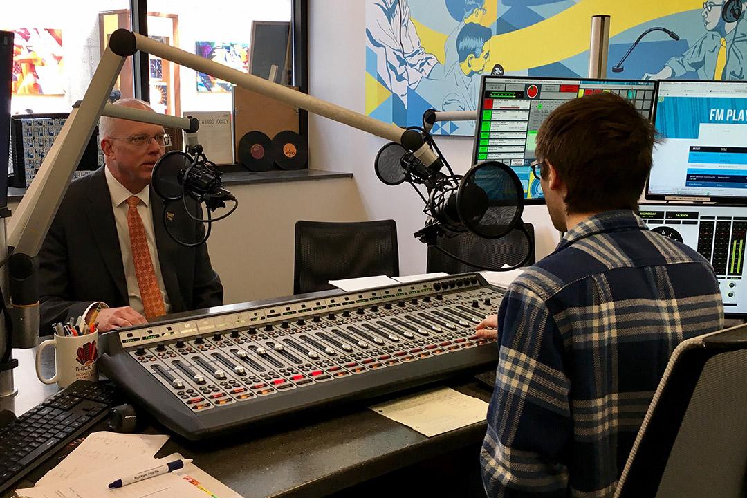 'President Munson talking to student in radio station.'