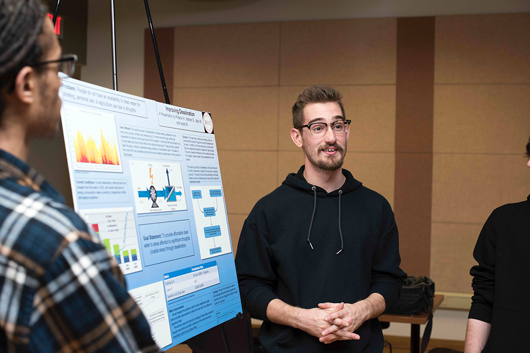 'student presenting poster.'