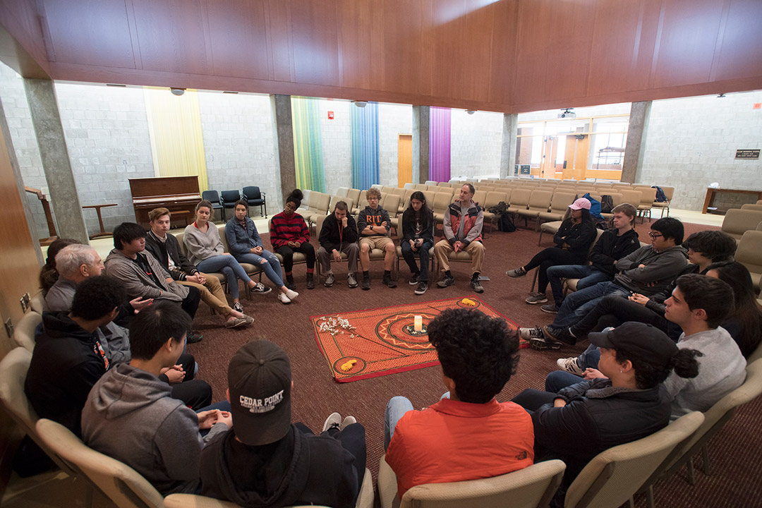 Large group of students sits in circle having discussion.