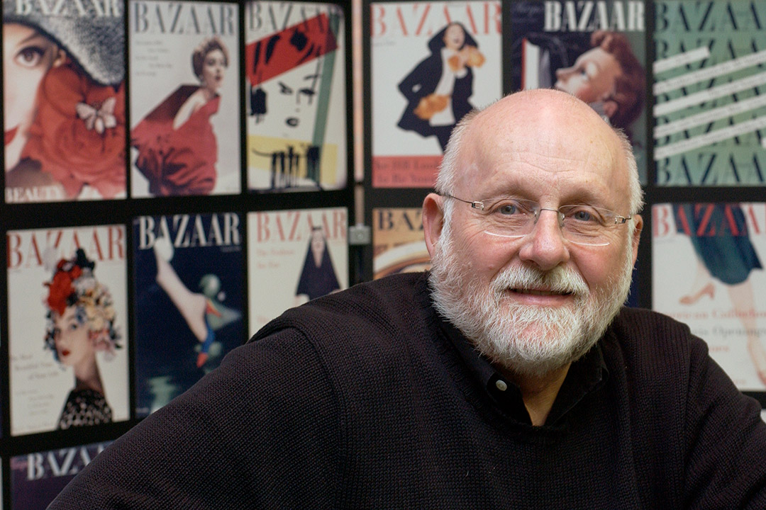 R. Roger Remington with Harper's Bazaar magazines in the background.