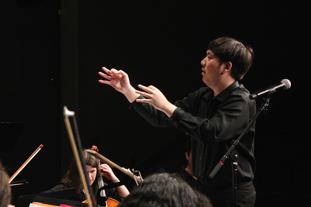 student conducting orchestra.