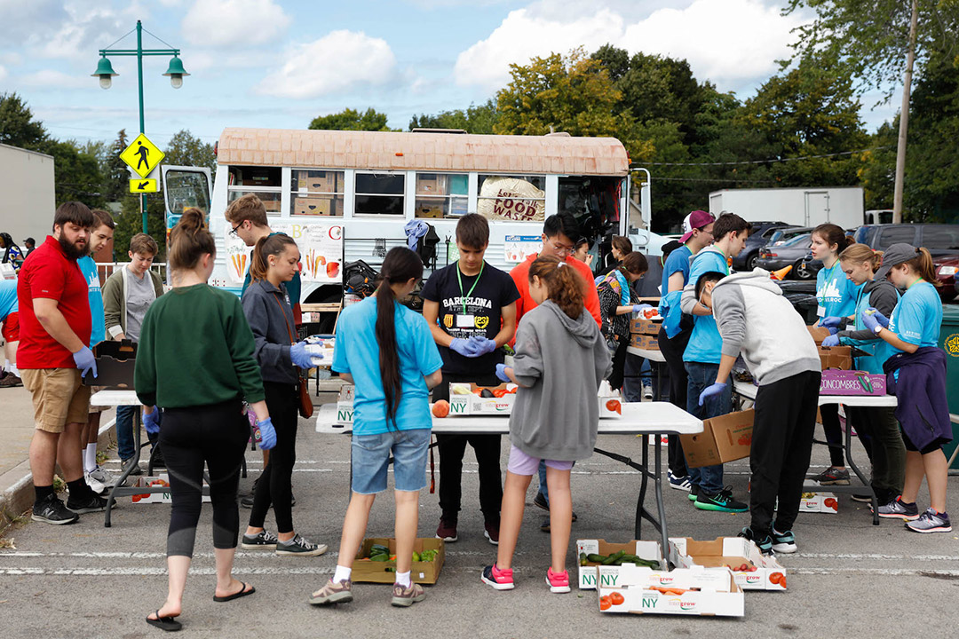 students crowding around tables of produce at a public market.