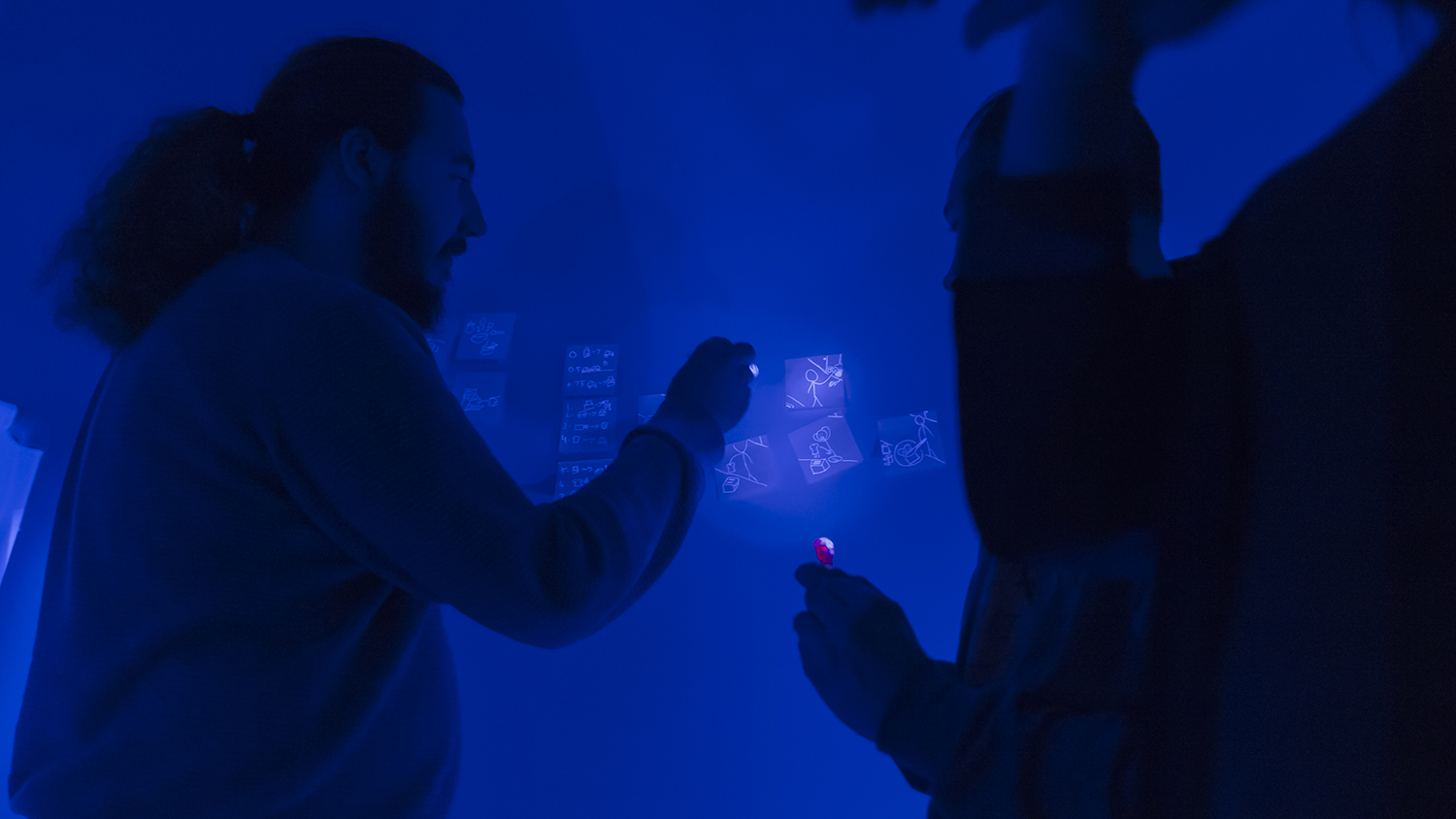 'Students investigate the use of invisible ink with the lights turned off.'
