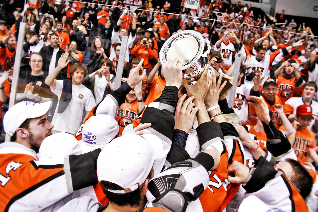crowd of RIT hockey players holds up trophy.