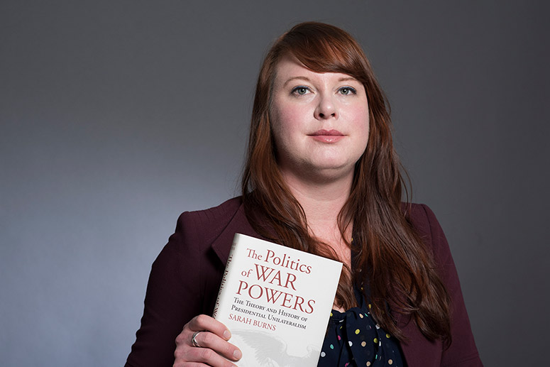 professor holding book titled: The Politics of War Powers.