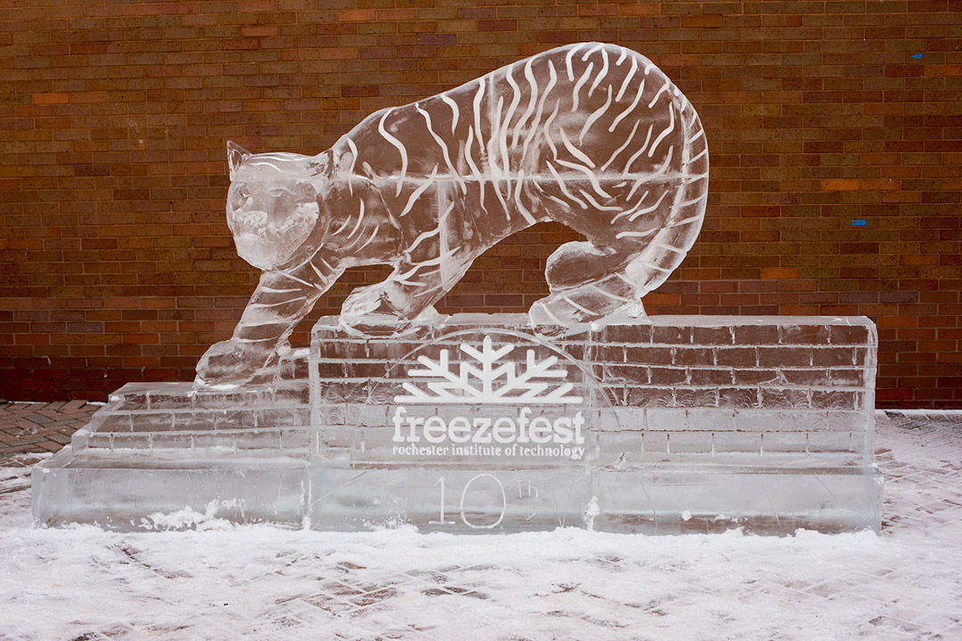'ice sculpture of tiger standing on brick wall.'