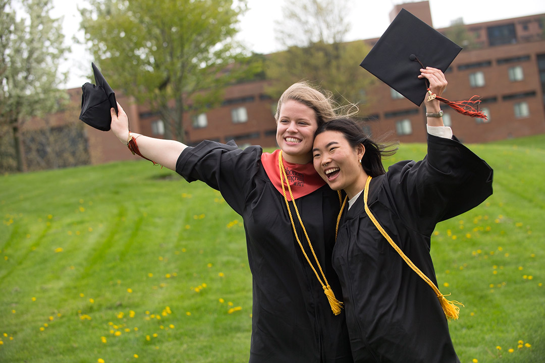 two graduating students wearing cap and gown smiling for photo.