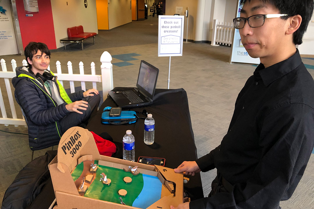 student playing cardboard prototype of a pinball machine.