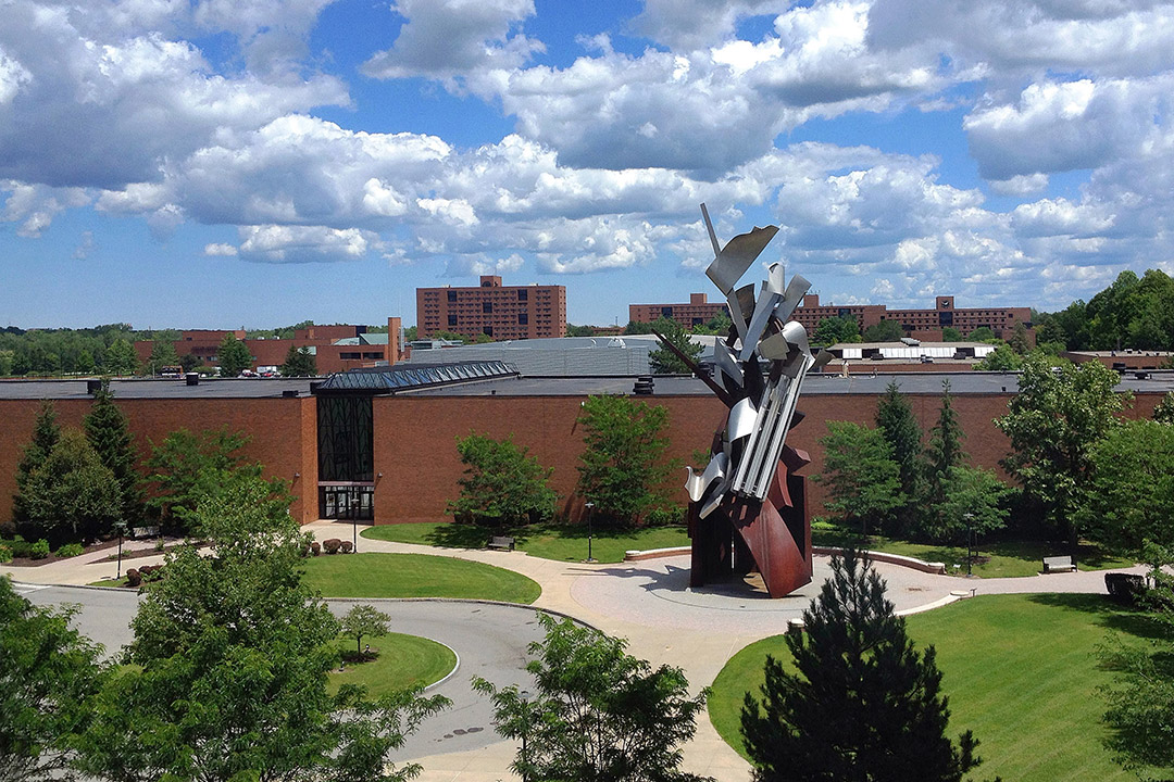 outdoor metal sculpture near brick buildings.