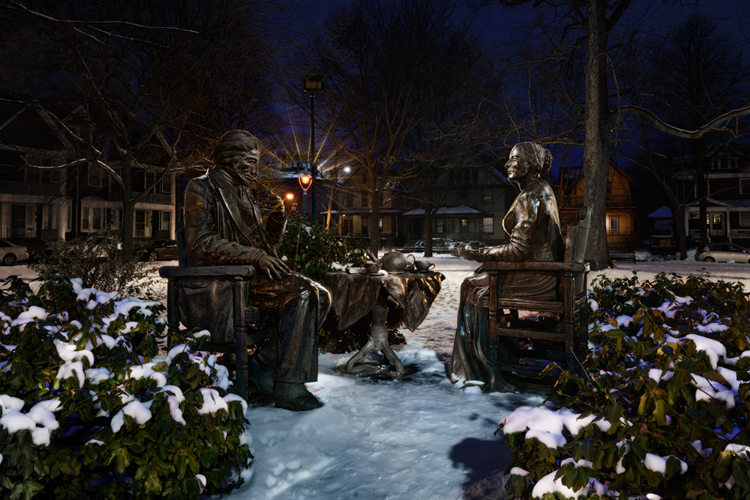 'nighttime shot of statues of Susan B. Anthony and Frederick Douglass.'