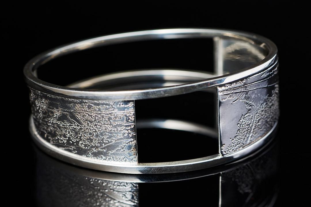 silver cuff-style bracelet.
