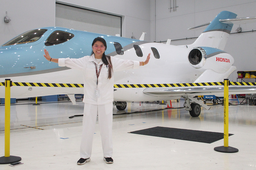 student posing in front of a new jet.