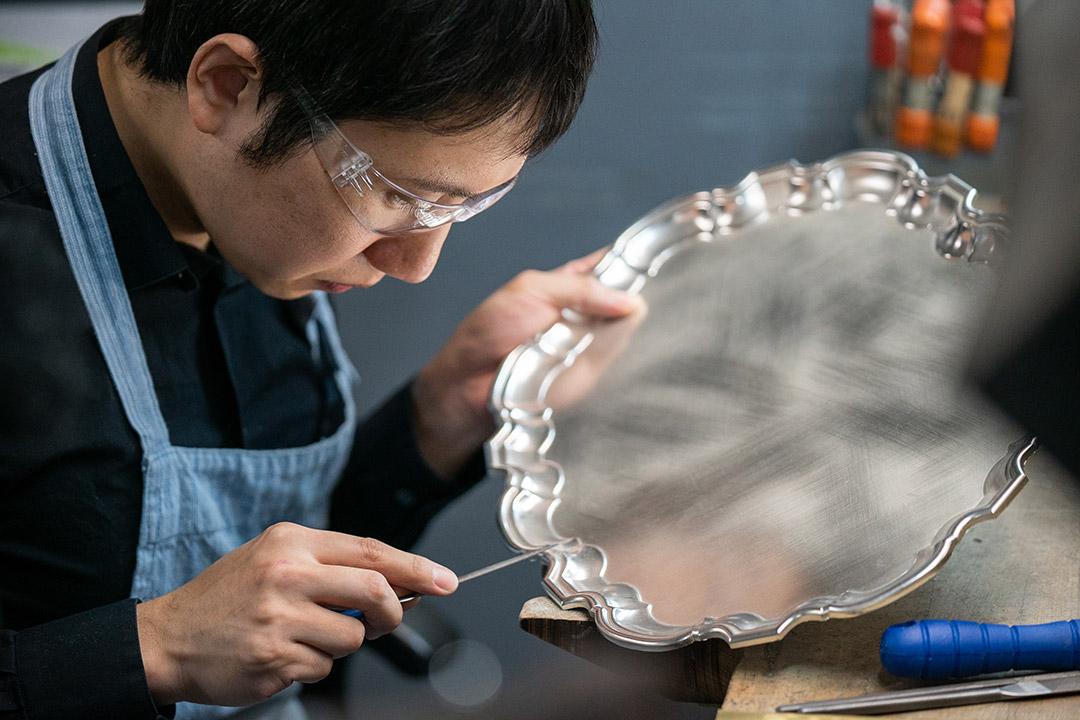 Kibaek Sung metalsmithing a silver platter.