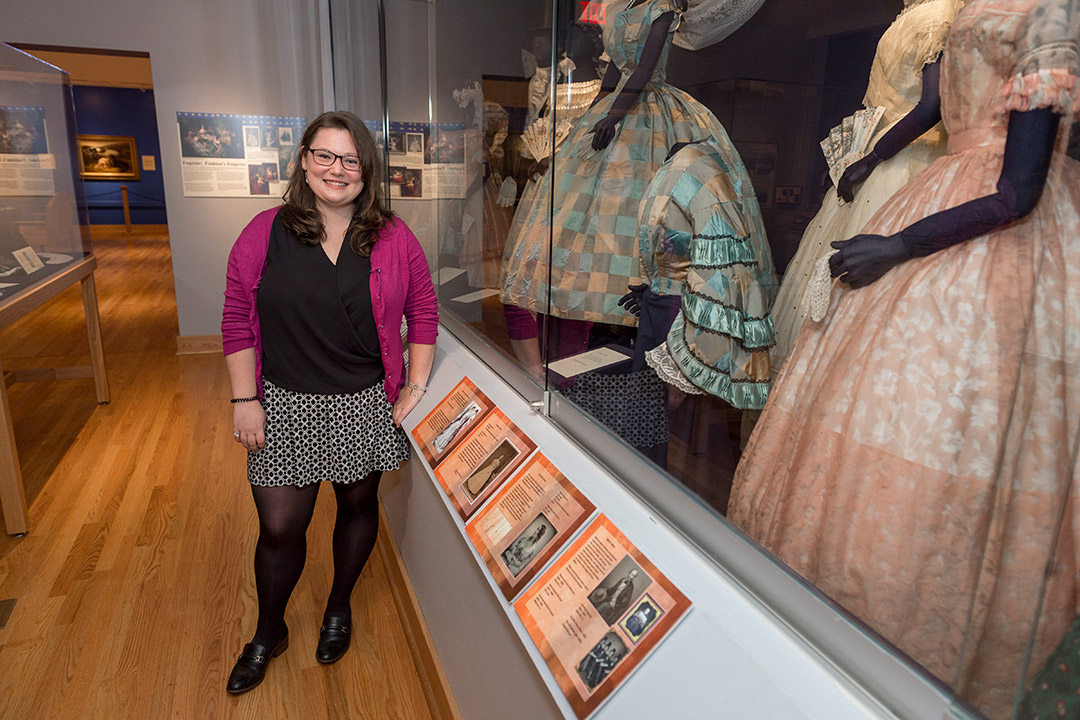 student posing with museum exhibit of women's dresses.