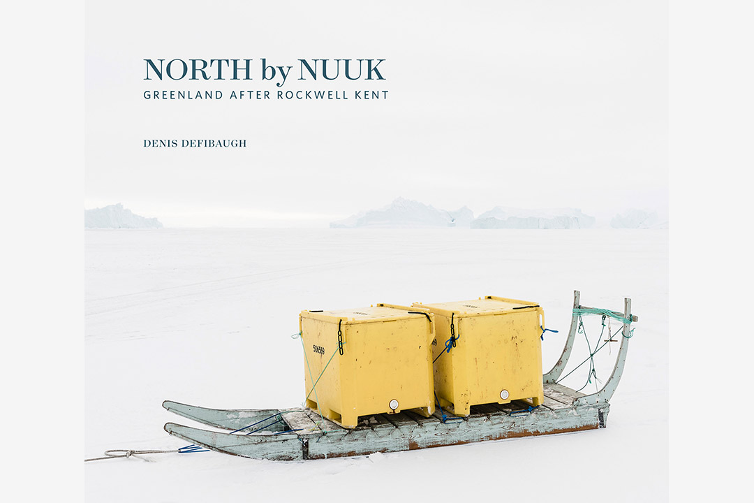 'North by Nuuk' book cover, featuring two yellow boxs on wooden sled on a sheet of ice.