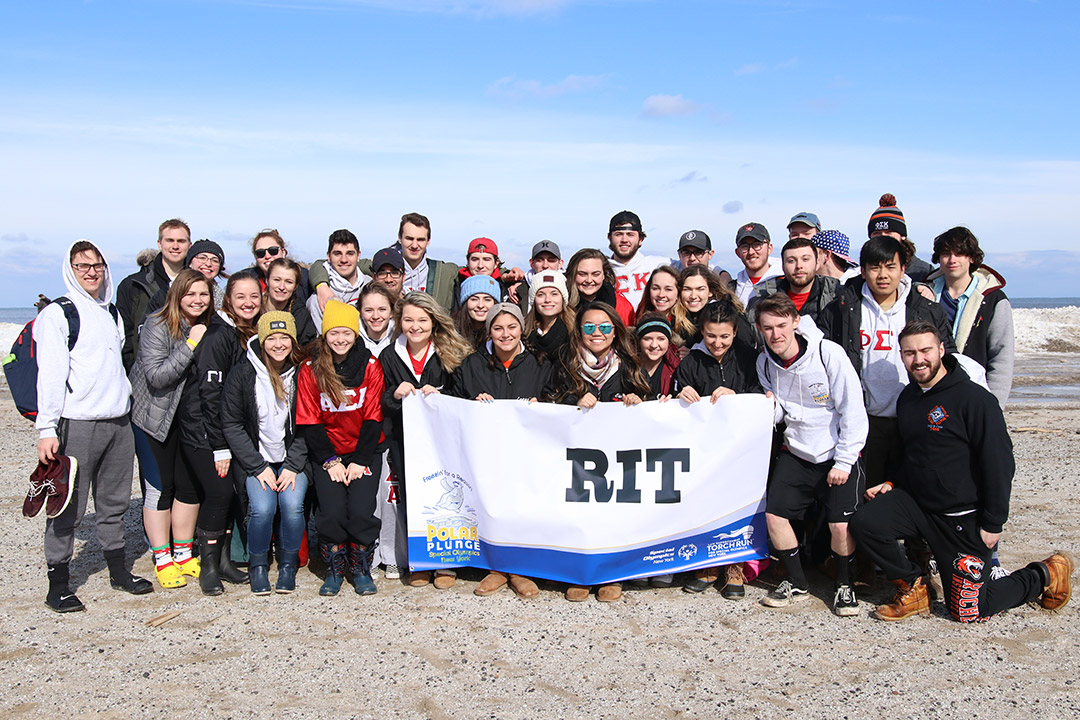 team of students on beach of Lake Ontario in winter.