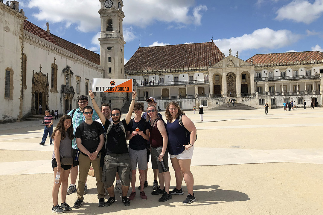 "'group of students holding ""RIT Tigers Abroad"" banner in square in Portugal.'"