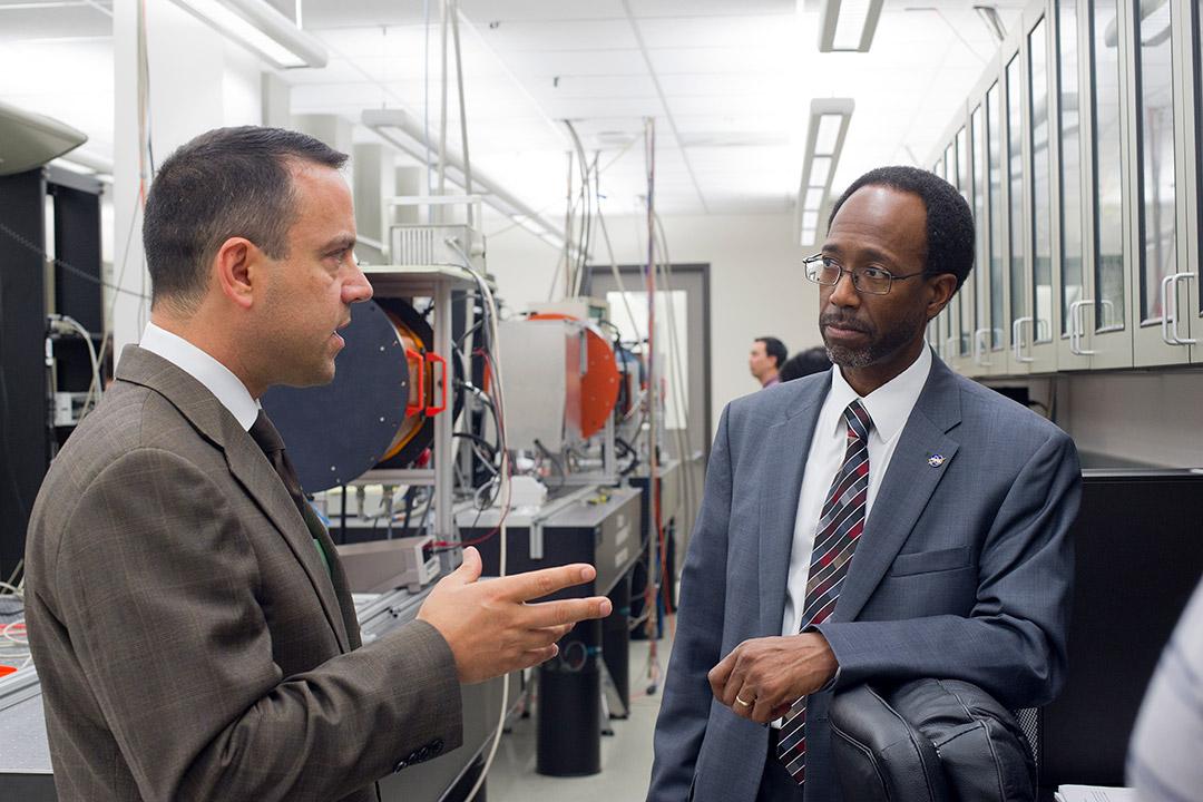 two men talking in lab.