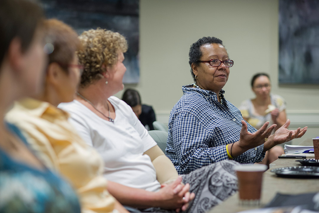 professor speaking while sitting at table with other women.
