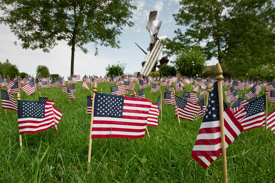 small American flags stuck into the lawn in front of a metal sculpture.