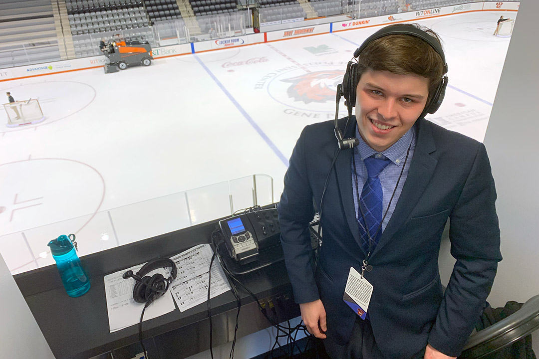 student wearing headset in press box in ice arena.