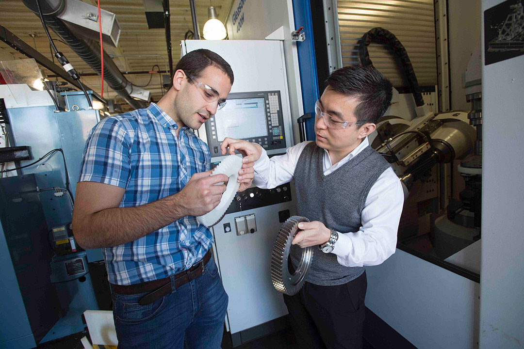 professor and student looking at large metal and plastic gears.