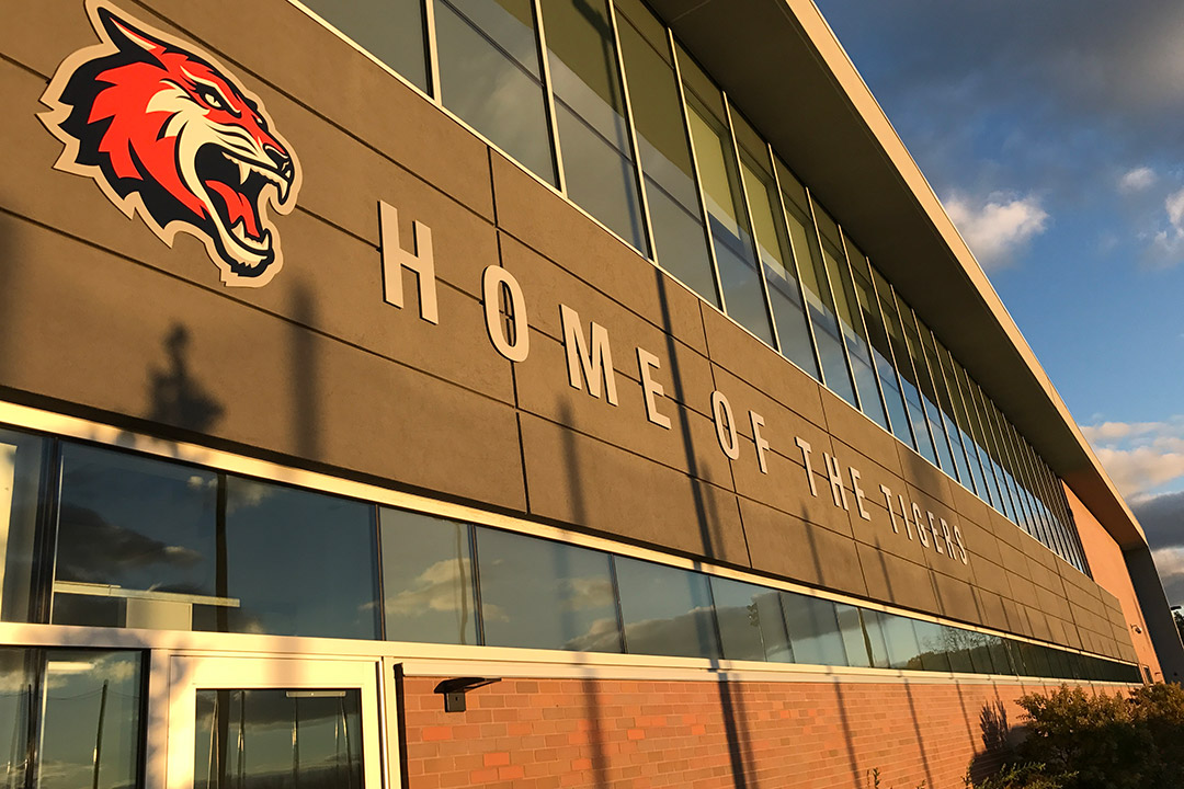 exterior of Gene Polisseni Center with banner that reads: Home of the Tigers.