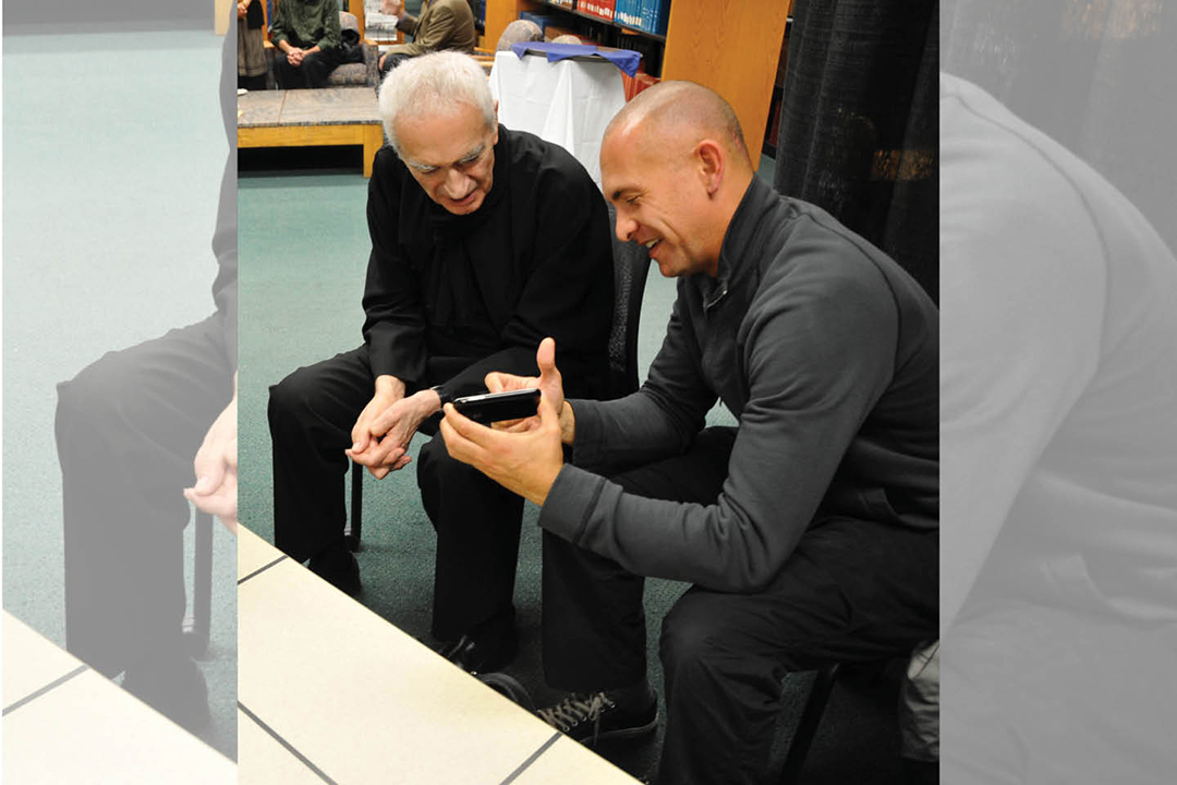 Josh Owen and Massimo Vignelli look at a student's design.