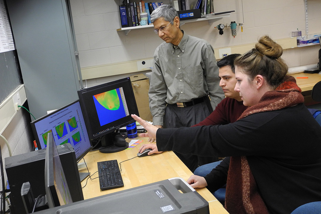 researchers looking at infrared images on computer screens.